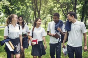 Five high school students walking together outside carrying school supplies