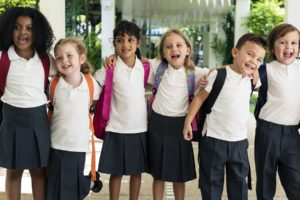 Six young students in uniforms in line with arms around each other happy